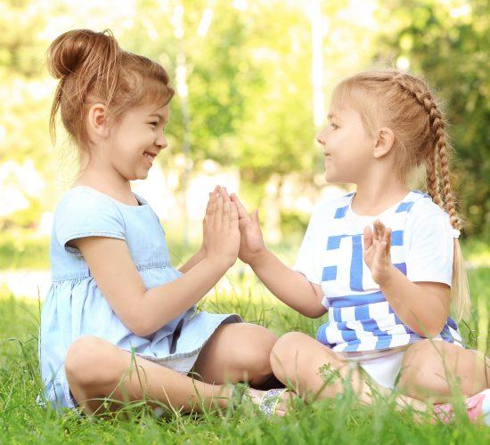 Cute little girls sitting on green grass in park