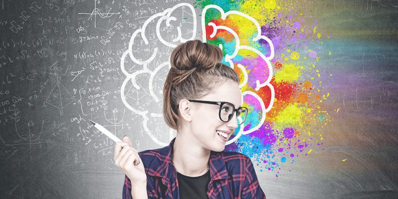 Smiling confident young hipster woman wearing a checkered shirt, a black t shirt and glasses holding a pen and looking sideways. A blackboard with a colorful brain sketch