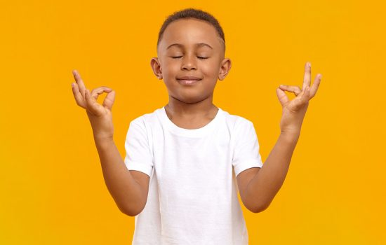 Peaceful calm little boy of African appearance wearing casual t-shirt keeping his eyes closed and smiling, meditating isolated in studio. Conscious dark skinned schoolboy practicing meditation
