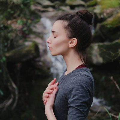 Young woman practicing breathing yoga pranayama outdoors in moss forest on background of waterfall. Unity with nature concept