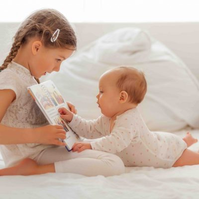 Mädchen liest ihrer kleinen Schwester etwas vor