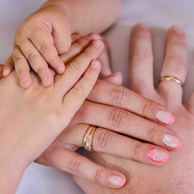 three hands of the family, the child, the mother and father. The concept of unity, support, protection and happiness.