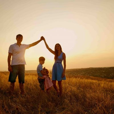 Happy family in the field at sunset in the summer autumn.
